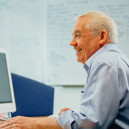 Man at his desk laughing with someone out of sight
