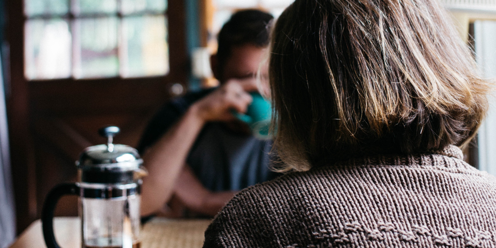 Back of woman's head as she sits drinking coffee