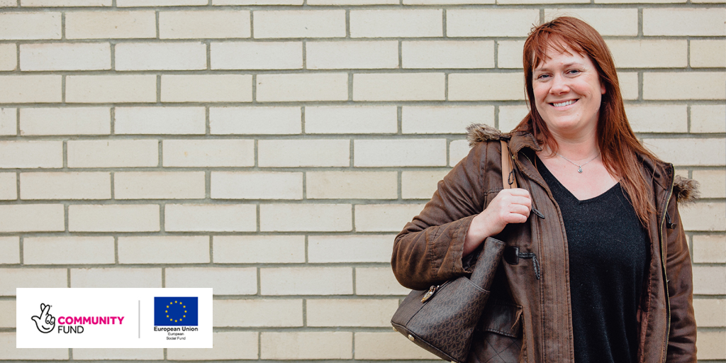 Woman smiling against brick wall