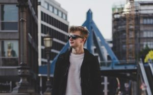 Young man walking through a city looking content