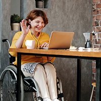 lady in a wheelchair at work on a video call smiling and waving