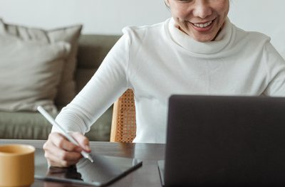 Lady watching a video on her laptop, smiling and taking notes