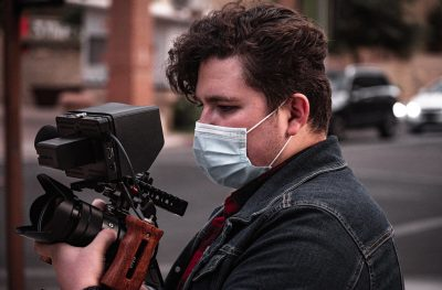 Young man holding a video camera whilst wearing a mask