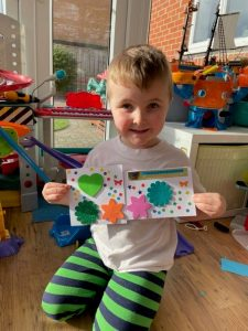 4 year old child holding the greeting cards he has made and smiling