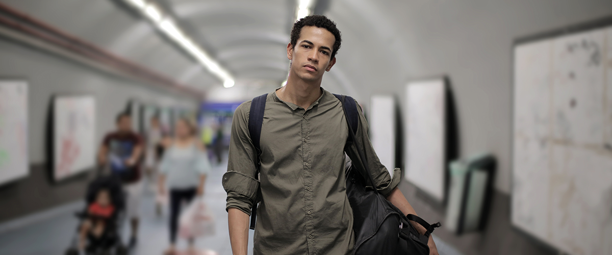 young man stood in the underground tunnel of a train station
