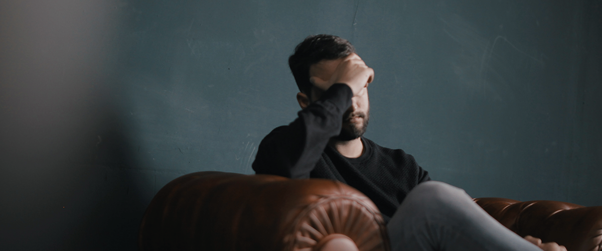 Middle aged man, sat on a sofa with his head in his hands