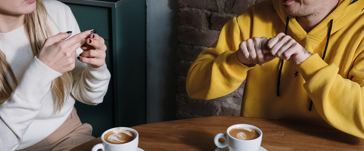 Man and a Woman having a sign language conversation over coffee