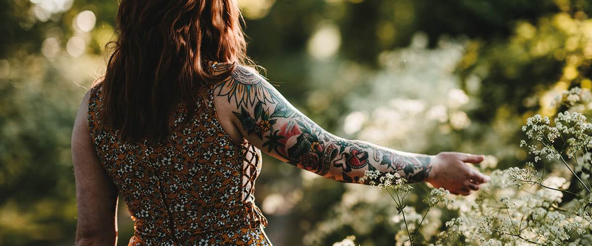 A tattooed lady walking away from camera, running her hands through flowers